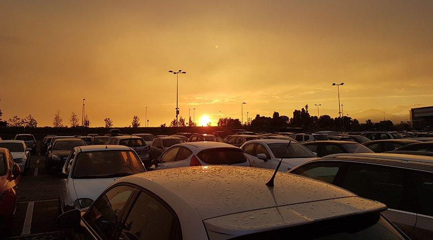 importuojami automobiliai iš JAV saulėlydžio fone